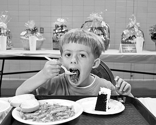 TASTY: Corey Cook, 4, of Boardman filled his plates with spaghetti and cake for a fundraiser by the Mahoning Valley 9/11 Memorial Committee. The Cook family's contributions on Sunday will go toward a memorial for victims of the Sept. 11, 2001, terrorist attacks.