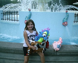 This is my daughter Kylie Thomas on her 7th birthday.  She wanted to go to Pittsburgh for her birthday.  This is her at the fountain at Kennywood Park with the stuffed animals she won herself.