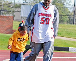 BIG AND SMALL STEPS: Aidan Slocum, 6, of Boardman walks with YSU basketball player Jack Liles of Maryland in the inaugural  Coaches vs. Cancer 3-mile walk at Youngstown State University's outdoor track. Aidan is the grandson of head coach Jerry Slocum of Boardman.