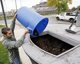 Dan Kuzma, YSU recycling manager dumps bark mulch into a food waste composting device outside Christman Dining Hall on the YSU campus Monday. Mulch is mixed with food waste and turned into compost to be used on campus.