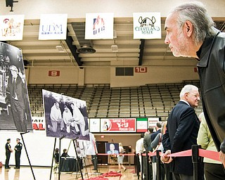 Lewis Ramos of Canfield leans over the barrier to get a closer look at a photo while in line at Dom Rosselli's calling hours. Photos and a memorial for Rosselli were set up in the YSU gym.