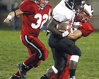 CANFIELD - NILES - (32) Alan Koren Jr. and (33) Nico Wagner bring down (14) Blake Jackson of Canfield during their game Thursday night in Niles.