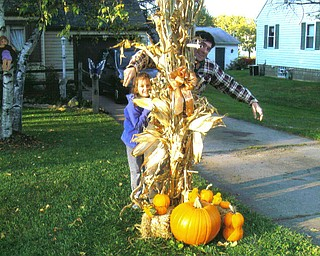 Autumn and Andy Murzda of Hubbard play scarecrow behind pumpkins.