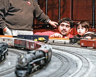 FAMILY AFFAIR: Frank Carbon of Boardman and his son, Gregory, 2, watch a model train round the bend during the YMRA event.