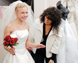 BEAUTIFUL AND FREE: Judy Gibbons of Macedonia tries on a wedding dress at Evaline's Bridal store in Warren. Beside her, shop owner Lori Dubasik assists Gibbons with her dress during an event giving military brides free and deeply discounted dresses.