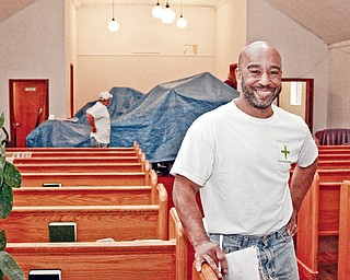 UPLIFTING WORK: Roy Thomas, co-founder of the Positive People Group, stands in the sanctuary of Oak Baptist Church, 320 Elk St., Youngstown, where tarps cover the altar area. The croup cleaned up and painted last weekend at the church, which had been damaged by vandals.