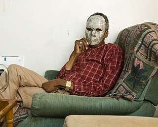 "Wilbur, a straight, black male with HIV in Youngstown, reclines in his living room.  His face is covered with a Halloween mask to hide his identity.  Although he said he hasn't experienced much discrimination, he is careful about disclosing. ""Years ago, a friend of our family had cancer. When we went over there, we were told to cover the toilet seat. That's how HIV is perceived now,"" he said."