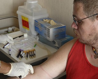A nurse at an HIV/AIDS clinic takes weekly blood samples from Michael Bushara, a gay, white male in Youngstown. Medical check-ups and the pill regiment divide the day, Michael said.