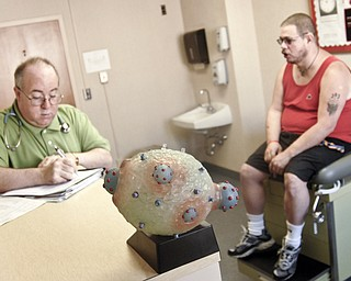 Michael Bushara, a gay, white male from Youngstown, discusses possible reasons for his lowered T-cell count with a doctor at an HIV/AIDS clinic. In the foreground is a model of dark blue HIV viruses replicating within a healthy human T-cell.