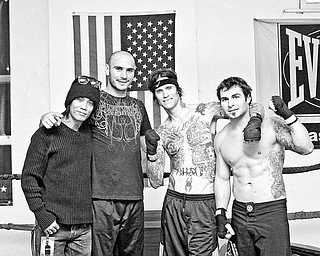 Guitarist Stevie D. of Buckcherry, World Middleweight Champion Kelly Pavlik, Vocalist Josh Todd of Buckcherry and Buckcherry's personal trainer and private security chief Dan Abell pose inside the ring at Southside Boxing Club Saturday