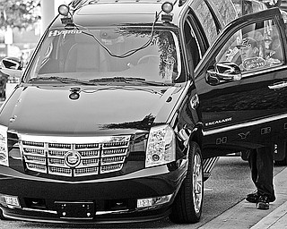 A driver prepares to unload a new 2009 Cadillac Escalade 2WD Hybrid, onto the floor of the Los Angeles Convention Center, for the Los Angeles Auto Show  Tuesday, Nov. 18, 2008. New cars are supposed to be the main attraction when the Los Angeles Auto Show kicks off, but dreadful U.S. sales, bailout hearings in Congress, and General Motors' decision to all but pull out of the event are sure to be the elephants on the showroom floor.