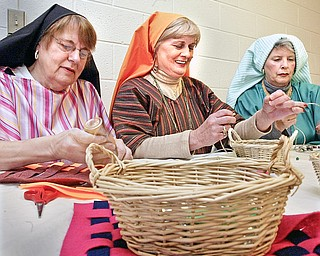 Churchill United Methodist Church in Liberty will host a Night in Bethleham. Dressed in period attire these members of the church L-R  Pat Marsh, Marlene Flickinger and Jan Ferry prepare craft items for the event.