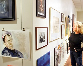 Judy Kay, a volunteer at the Art Outreach center in the Eastwood Mall looks over art on display there.