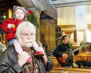 Bill Moran of West Middlesex holds his grandaughter Michaela Garltic, 1, on his shoulders during Chrsitmas at Old Mill in Mill Creek Park Sunday. In background is Roland Kausen, a Cleveland based musician who entertaining at the event.
