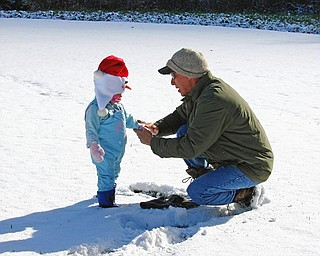 "Jeff Hum enjoys the first snow with his niece, Jaylianna Wilt. ""Uncle"" Jeff was putting her mitten back on after throwing snowballs at ""Aunt"" Karen. Photo taken by Karen Hum of Canfield."