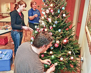 All hands on - The Mahoning Valley Historical Society  tree is being decorated by Leann Rich (farthest from camera to closest )- Rebecca Whittenberger and Anthony Worrellia  - More than 30 Mahoning Valley groups and agencies decked the halls of Fellows Riverside Gardens' D.D. and Velma Davis Visitor and Education Centr for Mill Creek MetroParks' annual Winter Celebration.