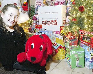 LENDING A HAND: Alexis Cintron, 8, of Austintown, shows off some of the gifts she's collected during her second annual Toys For Tots drive. She said she decided to start her own drive last year and hopes to double the 250 toys she collected in 2007. Toys can be dropped off at Spalon in Howland through Dec. 17.