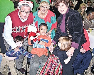FOR THE KIDS: Children, parents and staff of The Rich Center for Autism enjoy food, music and seasonal fun at the third annual holiday party sponsored by Merv and Marlene Hollaner. Merv Hollander, his wife, Marlene, and Bernadette Kovach share in the fun with center pupils, from left, Colin Brogan, Nathan Tucker and Ellie Brogan.