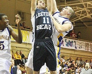 REACHING FOR IT: Leetonia's Matt Newton (11) is fouled by McDonald's David JOhn as he dives to the oop in Friday's game in McDonald. The Blues Devils defeated the Bears, 68-55.