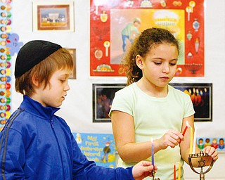 Dylan King and Abigail Sharf  third graders at Akiva Academy light the Menora  - Each night during Chanukah Jews light candles in a special candelabra called a Menorah (Hebrew: Hanukiyah). The center candle, called the Shamash, is always the first candle placed in the Menorah and the first candle to be lit each night. The remaining candles are placed and lit in a specific order depending on the night of the celebration.