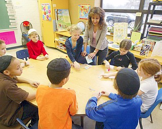 Tirtra Kohan, third grade teacher at Akiva Academy in Liberty, watches as her student  play the dreidel - it is one of the best known symbols of Chanukah. A four-sided top with a Hebrew letter on each side, the dreidel is used to play a fun Chanukah game of chance.