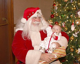5 month old Ella Rose Solak sits on Santa's Lap on Christmas Eve at the Menichini Family Christmas Party in Lowellville