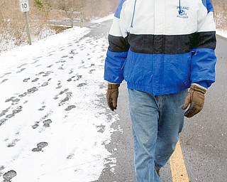 "TAKING A WALK: Dave DiRienzo, 55, of Beaver Township, walks along East Golf Drive at Mill Creek MetroPark. DiRienzo, a teacher in Poland, said he typically takes a 40- to 50- minute walk once or twice a week through an area park, although he admits to going out ""a lot more during the summer months."""