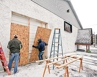 CLOSING A BAR: The Cell, a bar at 221 Belmonst Ave., is boarded up after Judge John M. Durkin of Mahoning County Common Pleas Court issued a temporary restraining order that declared it a public nuisance. Telly Dutton, left, and David Gordon, of National Fire Repair in Youngstown, apply the plywood.