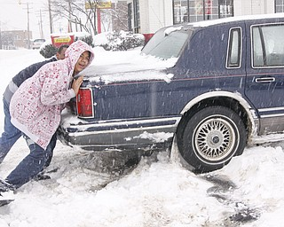 Sean Runkle and his son Isaiah of Youngstown push their Lincoln Towncar after getting stuck in the McDonald's parking lot on Mahoning Ave, Saturday January 10, 2009