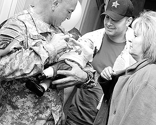 Staff Sgt. Rudy Santibanez Sr of Toledo holds his new granddaughter Aliviah (1 mth) as he stands next to his son Rudy Jr. and Rudy Sr's wife Joyce. Rudy Sr. just returned home from his 3rd tour in Iraq