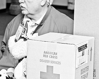George Braindard of Austintown talks about the American Red Cross Disaster relief. Supplies for emergency relief sit on the table in front of him