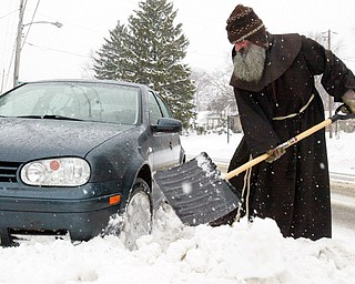 Rev. Vit Fiala, a priest at Shrine of Our Lady, Comforter of the Afflicted, 517 S. Belle Vista Ave in Youngstown, digs his car out after sliding into a snowbank in front of the shrine Tuesday. With the help of a few passing motorists and a Vindicator photographer he was on his way.