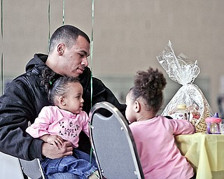 Sergio Rivera of Youngstown with his daughters London Rose (1) on his lap and Nevaeh (2) attend the 3rd annual City-Wide baby shower at McGuffey Center