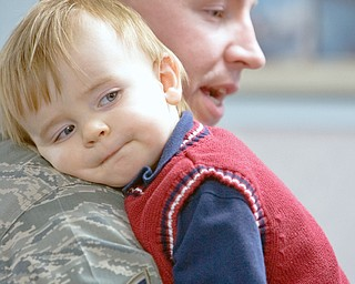 DAD'S BACK: Grayson Bonar, 1, of Vienna, rests on ther shouler of his father, Tech. Sgt. Jason Bonar. It's the first embrace between the two since Jason Bonar left for duty in Kirkuk, Iraq, more than six months ago. He returned home Thursday afternoon at Youngstown Air Reserve Station in Vienna with 12 other members of the 910th Security Forces Squadron.