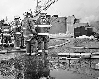 Some Pulaski Firefighters stand behind Parktown lanes as the building is destroyed by the fire, Saturday January 24, 2009