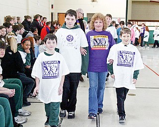 St Patrick School Hubbard students and brothers l-r Joey Fisher, 9, Billy Fisher, 12, and John Fisher, 10, walk with family friend and cancer survivor  Patricia Boyle of Hubbard during a Relay for Life event at the school Monday.