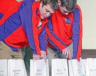 Youngstown Phantoms players Johnny Meo, left, and Doug Clifford light luminaries during a Relay for Life event at St Patrick School in Hubbard Monday.
