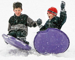 SOME SNOW IS FUN as Brian Yauger 8 and Jeffrey McAuley hold hands as they hit a bump on the park area in front of Poland Presbyterian church