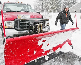 Snowplow driver Carl Dohar of Arrow Asphalt checks his plow while working in Liberty.