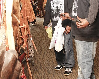 Brandon Albert (28) of Warren and Ariggle Moore (29) of Austintown look at a cane from Kenya in Kilcawley Center. The two attend YSU's African Marketplace every year. Its in celebration of Black History Month, Saturday February 7, 2009