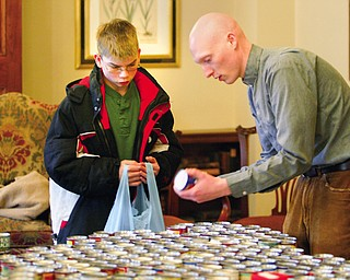 Packing his bag of crackers soup  and peanut butter Michael Syphard of Canfield and Reverend Jeremiah Williamson work together Youth Volunteer corp of the interdenominational Youth Coalition as part of the  soup crackers and peanut butter to area seniors