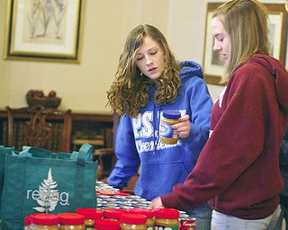 Packing up the goodies  Payton Maurer of Poland and Ciara Oslin of Boardman check the jars of Peanut butter as the Youth Volunteer corp of the interdenominational Youth Coalition packed up food and crackers at St Johns Church in Youngstown