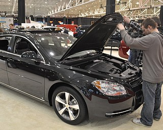 Inspecting a Chevrolet Malibu at the 2009 Cleveland Auto Show