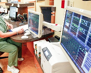 Jerri Nastase, a unit secretary at Mahoning Valley Hospital in Boardman at work near telemetry monitors in the hospital.