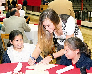 Kelsey Gurganus, middle, of YSU's womens basketball team gives her autograph to Marissa, left (8 1/2) and Gianna Lellio of Lowellville, right (10 1/2)