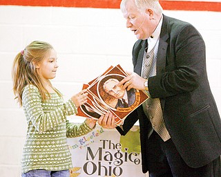 Jim Kleefeld gives photos of Ohios 8 presidents to Allison Cooper 4th grader as part of his THE MAGIC OF OHIO show to CH Campbell in Canfield.