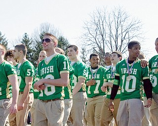 Grand marshals and state championship winners, Ursuline's football team, walks along market street during the 31st annual Mahoning Valley St. Patrick's Day Parade.