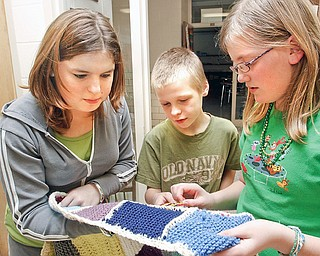 Kristin Boyd (14) Brett Rodgers (12) and Alexis Ramsey (12) look at the different knitted stitch squares made by everyone whose participating in the afterschool program at W.S. Guy Middle School in Liberty.