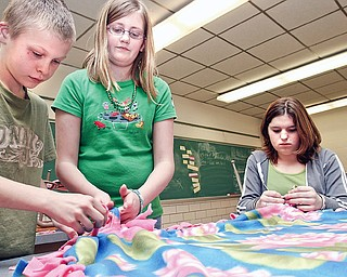 6th graders Brett Rodgers (12) and Alexis Ramsey (12) help make blankets along with 8th grader Kristin Boyd (14) for an after school program at their school, W.S. Guy Middle in Liberty