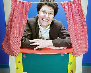 Executive Director, Suzanne Barbati, smiles through a puppet theatre at the Children's Center for Science and Technology on March 25, 2009.